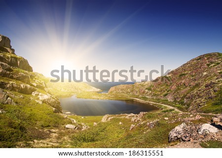 Mountain lake in the North. Moss-covered hills, and stunted vegetation. The Kola Peninsula. - stock photo