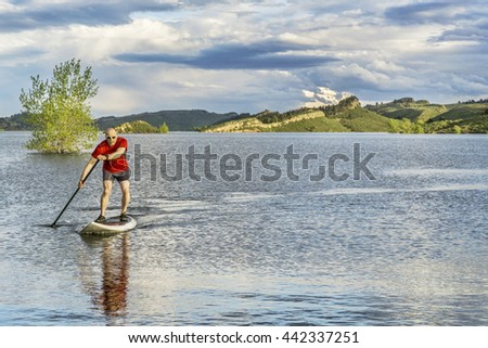 mountain lake landscape with a senior male paddling a SUP paddleboard with a copy space - Horsetooth Reservoir, Fort Collins, Colorado - stock photo