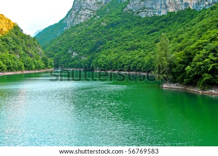mountain lake of fresh water produced for the production of electricity - stock photo