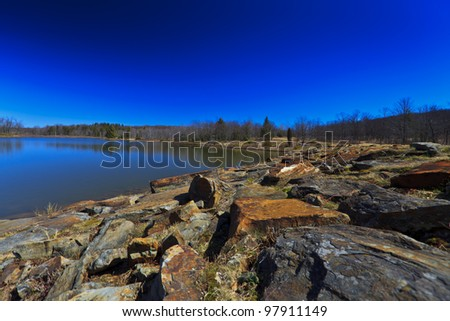 Mountain lake, old rocks and deep blue sky - stock photo