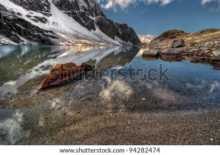Mountain lake sandy beach with pure reflection - stock photo