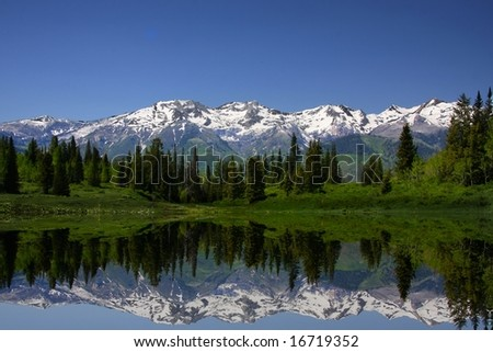 Mountain Lake showing reflections of snow capped mountains - stock photo