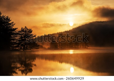 Mountain Lake Sunrise with silhouettes of trees reflecting in the water - stock photo