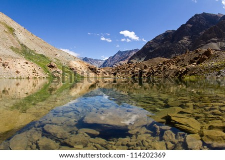 Mountain lake  with the beautiful reflections in water of the surrounding nature and blue sky