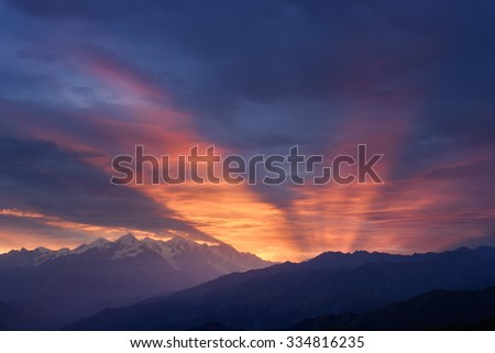 Mountain landscape at dawn. Beautiful sky with sunbeams and clouds. View from Mount Mkheer. Zemo Svaneti, Georgia  - stock photo