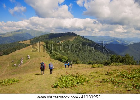 Mountain landscape background with blue sky and clouds. Large group of people sport clothing going on green grass meadow up towards forest and mountain peaks sunlight blue sky background - stock photo