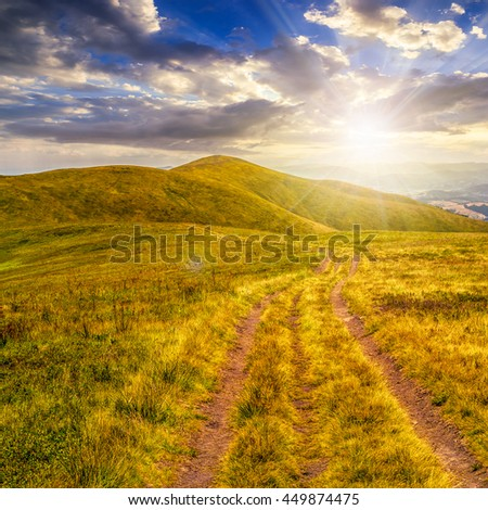 mountain landscape. curve path through the meadow on hillside in evening light - stock photo
