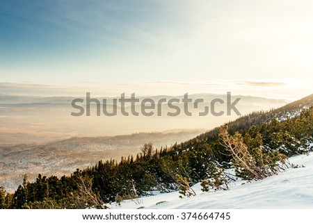 Mountain landscape during winter. Layers of mountains and valley from high cliff - stock photo