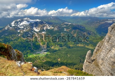 Mountain landscape in Austria. View from Loser peak over summits, rocky cliff and village in green valley, Dead Mountains (Totes Gebirge), group of mountains in Austrian Alps. - stock photo