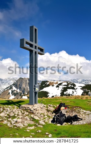 Mountain landscape in Austria. View of the cross and tourist backpacks at the top of Loser peak in Dead Mountains (Totes Gebirge), group of mountains in Austrian Alps. - stock photo