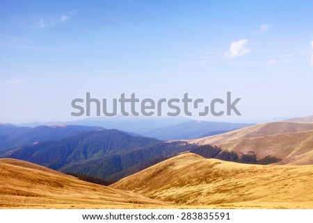 mountain landscape in hot summer day with blue mist over hills - stock photo