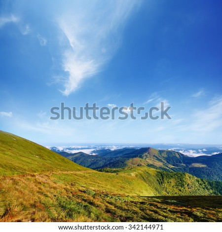 Mountain landscape in summer day. Blue sky with white clouds above green Carpathian hills - stock photo