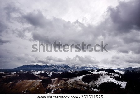 mountain landscape in winter with cloudy sky - stock photo