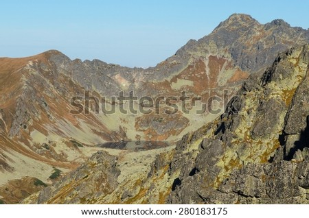 Mountain landscape. Picturesque view stretches over lake and rocky summits in Tatras National Park in autumn season. - stock photo