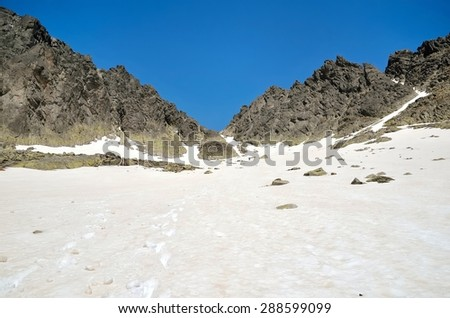 Mountain landscape. Picturesque view stretches over snowy trail leading to the high rocky summit in Tatra mountains, Slovakia.  - stock photo
