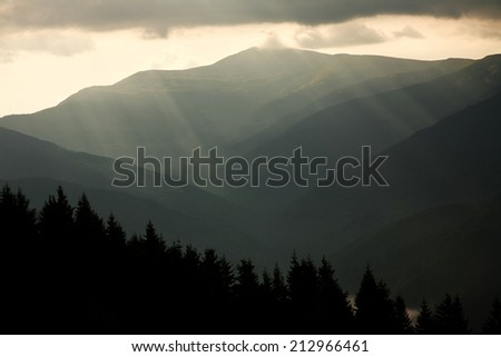 Mountain landscape, the sun rays through the storm clouds