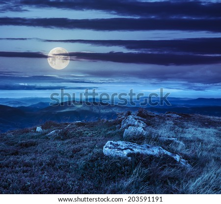 mountain landscape. valley with stones on the hillside. forest on the mountain under the moon light falls on a clearing at the top of the hill at night - stock photo