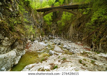 Mountain landscape with a creek flowing through a canyon on springtime - stock photo