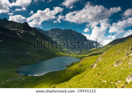 Mountain landscape with crystal river, and blue sky in Caucasian mountains. - stock photo