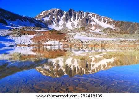 Mountain landscape with distant summits reflected by clear lake in the morning - stock photo