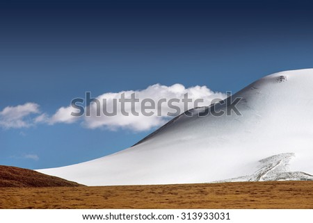 Mountain landscape with glacier, yellow steppe and clouds