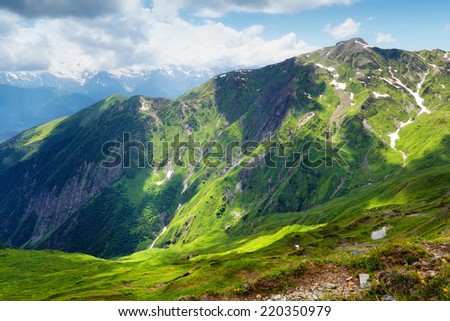 Mountain landscape with green grass and few snow - stock photo