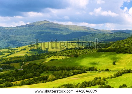 Mountain landscape with green pastures in summer day. Blue sky above hills