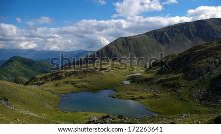 Mountain landscape with lake and clouds in the sky in Fagaras mountains, Carpathian mountains, Romania - stock photo