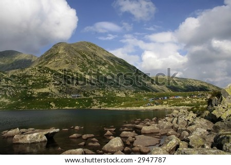 Mountain landscape with mountain lake and camp for tent
