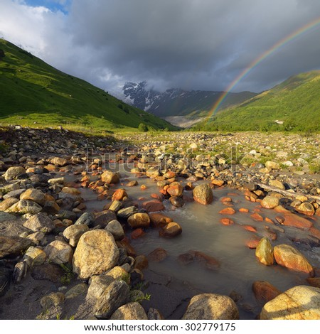 Mountain landscape with river and rainbow. Rainy day. Caucasus, Svaneti, Georgia - stock photo