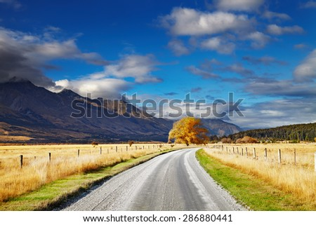Mountain landscape with road and blue sky, Otago, New Zealand - stock photo