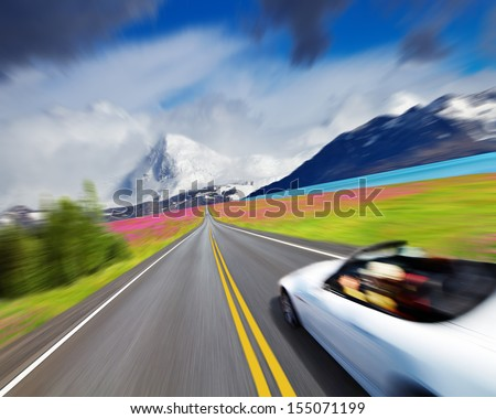 Mountain landscape with road and sports car in motion blur - stock photo