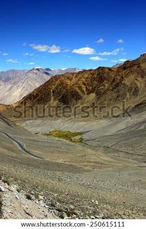 Mountain landscape with road and village in valley. Himalayas - stock photo