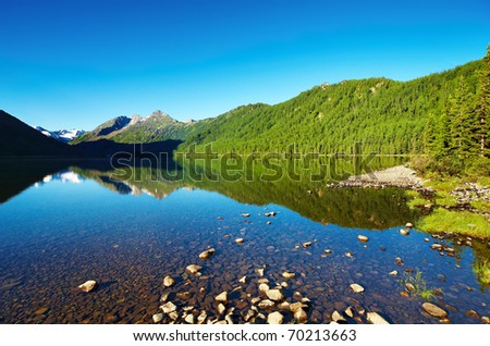 Mountain landscape with still lake and reflection - stock photo