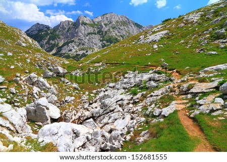 Mountain landscape with trail leading towards summit - stock photo