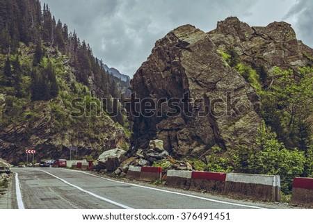 Mountain landscape with Transfagarasan road winding along rocky cliffs at high altitude in Fagaras mountains, Romania. - stock photo