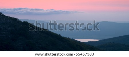 Mountain landscape with view of pink sunset