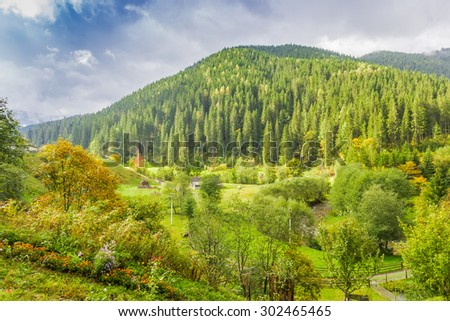 Mountain landscape with with rural outbuildings, forests and mountain ranges against the sky with clouds autumn.
