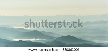 Mountain layer in morning sun ray and winter fog. - stock photo