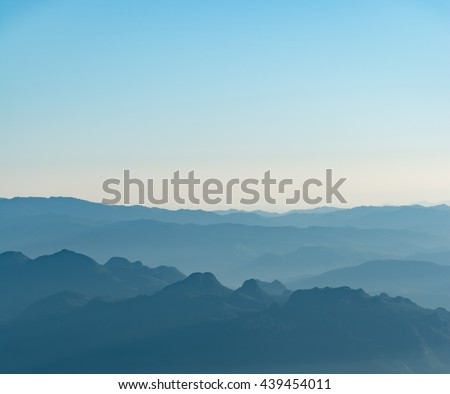 Mountain layer in morning winter mist and fog in blue sky. - stock photo