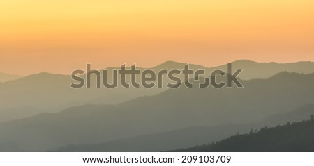 Mountain layers at sunset sky.