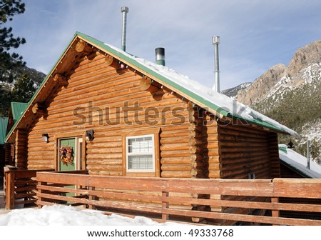 Mountain lodge in resort village surrounded by snow - stock photo