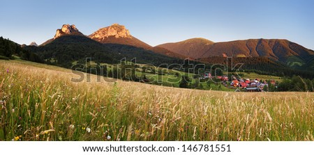 Mountain meadow panorama at sunset with village - Slovakia - stock photo