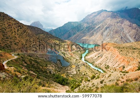 Mountain moraine river under cloudy sky in summertime - stock photo