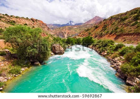 Mountain morraine river and red mountains under blue sky - stock photo