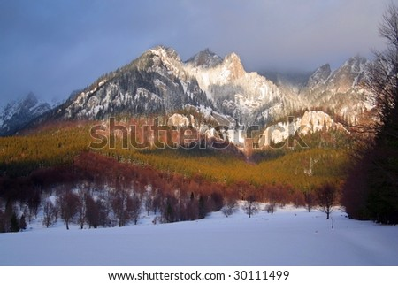 mountain painted with sunbeams on a stormy sky - stock photo