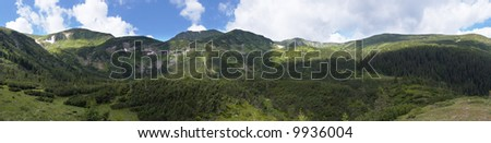 Mountain panorama view with juniper forest and snow remains on ridge in distance. Five shots stitch image. - stock photo