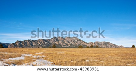Mountain panorama with golden grassy field in winter in the Colorado prairie near Boulder - stock photo