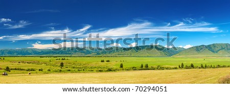 Mountain panorama with green field and blue sky - stock photo
