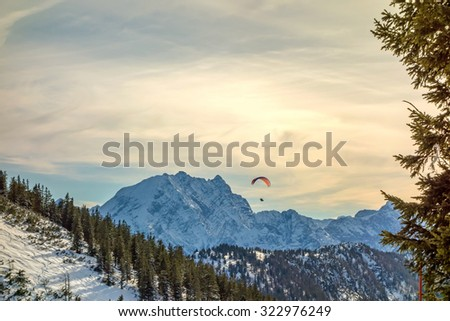 mountain panorama with paraglider at the sky - stock photo